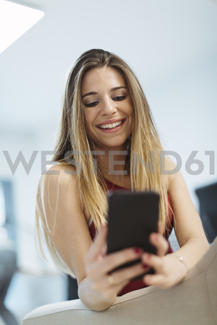 Smiling young woman using cell phone in the office - OCAF00226