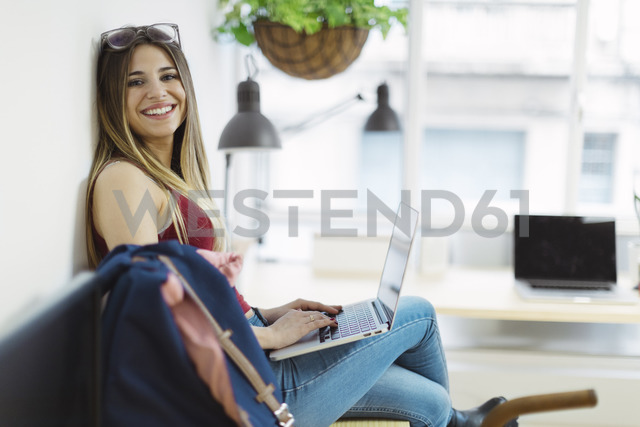 Smiling casual young woman using laptop in the office - OCAF00235