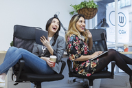 Two happy young women in the office with laptop and tablet - OCAF00238