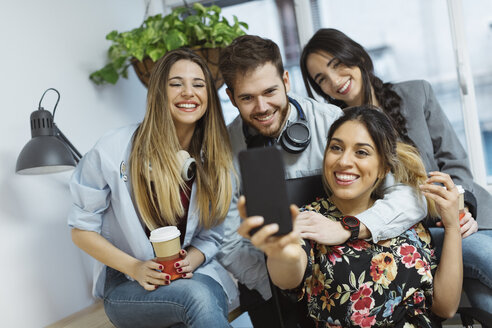 Happy casual coworkers in the office taking a selfie - OCAF00241