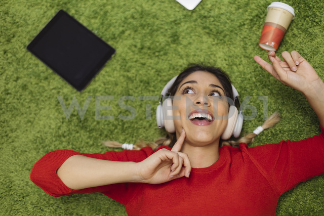 Happy young woman lying on carpet listening to music with headphones - OCAF00247