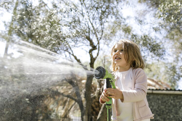 Smiling little girl playing with garden hose - KMKF00210