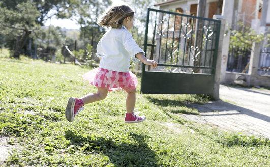Little girl running on meadow in the garden - KMKF00213