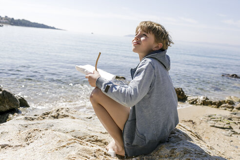 Boy sitting at seaside with self-made toy boat - KMKF00216