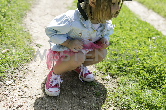 Little girl crouching on a meadow searching something - KMKF00219