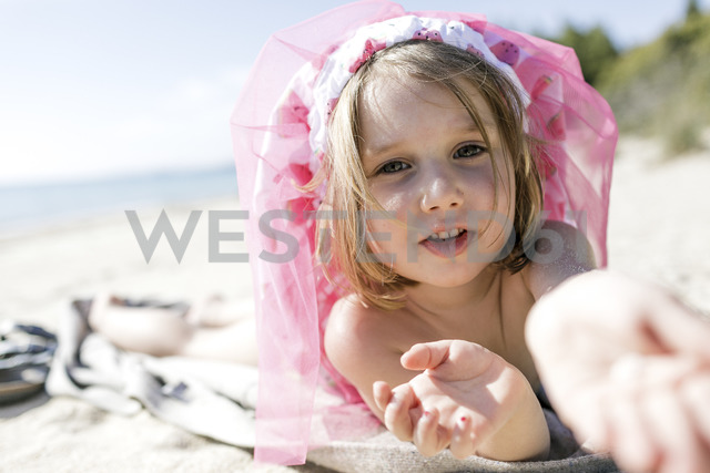 Portrait of little girl lying on the beach - KMKF00225