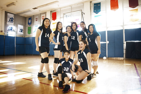 Portrait of happy female volleyball team at court - CAVF45284