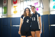 Portrait of smiling teenage girls standing in volleyball court - CAVF45287