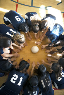 High angle view of girls volleyball team huddling on floor - CAVF45290