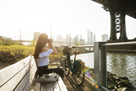 Woman photographing while sitting on bench by Manhattan bridge against clear sky - CAVF45365