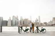 Couple taking selfie while standing by bicycles against East river in city - CAVF45374