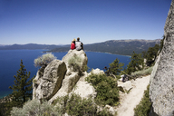 Couple sitting on cliff overlooking lake against clear blue sky - CAVF45383