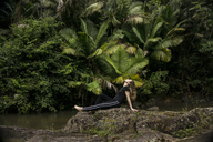 Side view of woman relaxing on rocks at lakeshore in El Yunque National Forest - CAVF45386