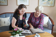Grandmother and granddaughter looking at photo album in living room - MASF06567