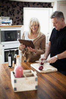 Couple in kitchen using digital tablet for recipe and cooking meal - MASF06587
