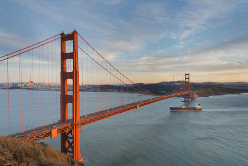 USA, California, San Francisco, Ship crossing Golden Gate Bridge in the evening - MKFF00362