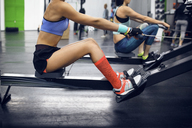 Side view of determined female athletes using rowing machine at gym - CAVF45470
