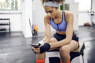 Female athlete using smart phone while sitting on box at gym - CAVF45473