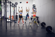 Female athletes exercising with medicine balls at gym - CAVF45491