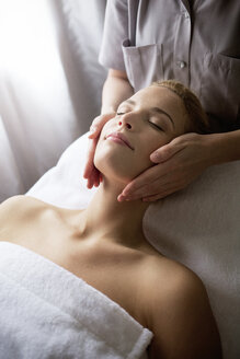 Female therapist massaging woman's face at spa - CAVF45578