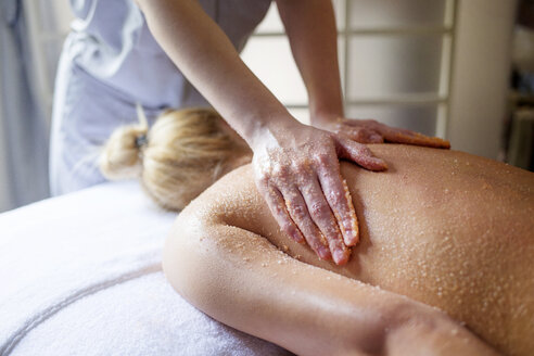 Midsection of therapist massaging woman's back in spa - CAVF45584