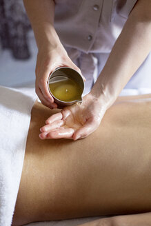 Midsection of therapist pouring essential oil on woman's back in spa - CAVF45587
