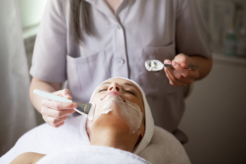 Female therapist applying facial mask on woman in spa - CAVF45596