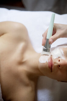 Overhead view of cream being applied on woman's face in spa - CAVF45599