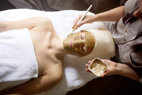 Overhead view of female therapist applying facial mask on woman's face in spa - CAVF45602