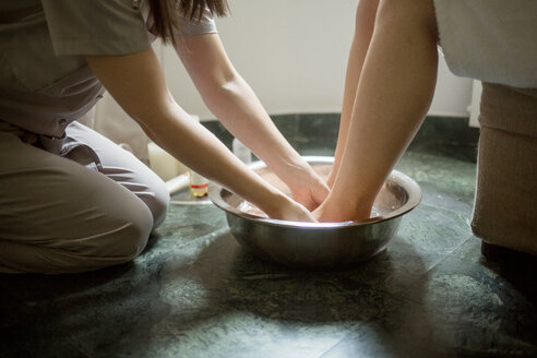 Midsection of therapist giving foot massage to woman in spa - CAVF45605