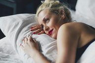 Close-up of thoughtful woman relaxing on bed - CAVF45659