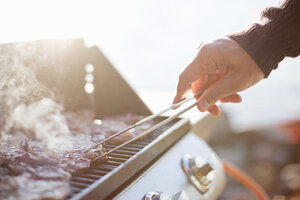 Close-up of man flipping beef with tongs on barbecue grill - MASF06595