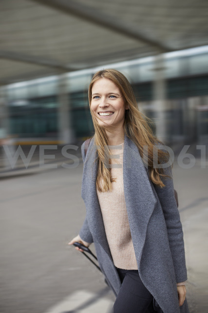 Portrait of confident businesswoman pulling suitcase at airport - PNEF00603