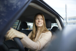 Portrait of smiling young woman sitting in car - PNEF00615