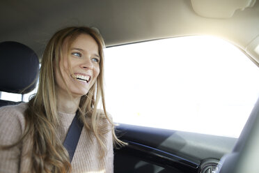 Portrait of laughing young woman in car - PNEF00618