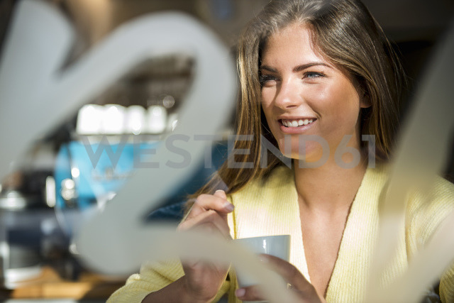 Portrait of smiling young woman in a cafe - DIGF03919