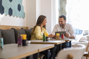 Young woman and happy man with tablet in a cafe - DIGF03922