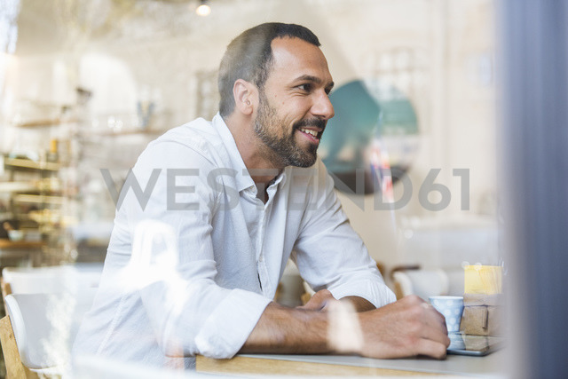 Smiling man with tablet in a cafe - DIGF03925