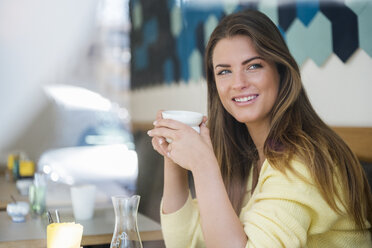 Smiling young woman in a cafe holding cup of coffee - DIGF03937