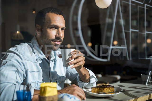 Smiling man drinking coffee and eating cake in a cafe - DIGF03940