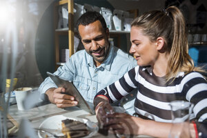 Young woman and man sharing tablet in a cafe - DIGF03943