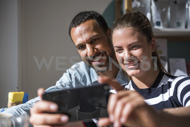 Happy couple taking a selfie in a cafe - DIGF03946