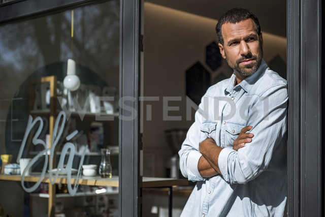 Man at entrance door of a cafe looking around - DIGF03949