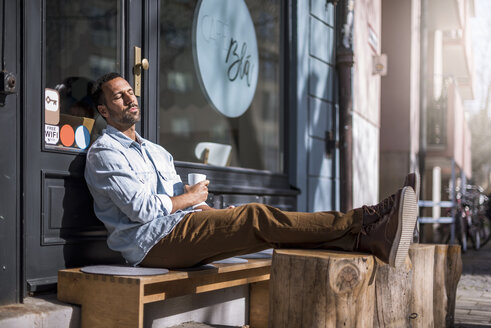 Relaxed man sitting outside a cafe enjoying the sunshine - DIGF03952