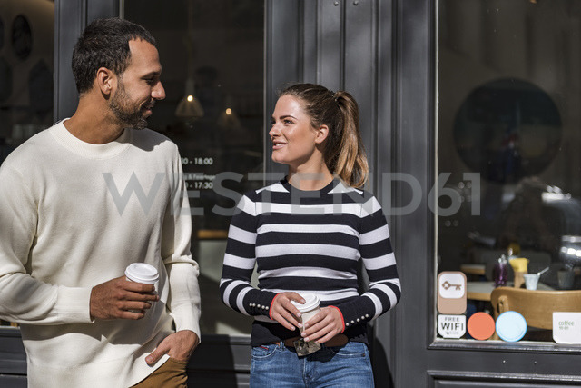 Man and woman holding takeaway cups outside a cafe talking - DIGF03955