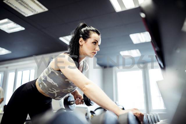 Woman exercising with dumbbells in gym - DAWF00614