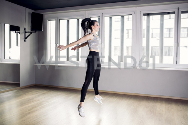 Woman doing a jumping exercise in gym - DAWF00617
