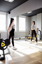 Woman exercising in gym looking in mirror - DAWF00623