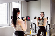 Woman lifting dumbbells in gym looking in mirror - DAWF00629