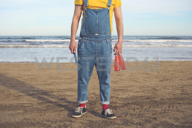 Man in dungarees standing on the beach holding bottles of soft drinks - RTBF01173
